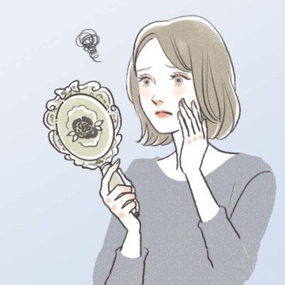 鏡を見て目尻のシワにうんざりしている女性